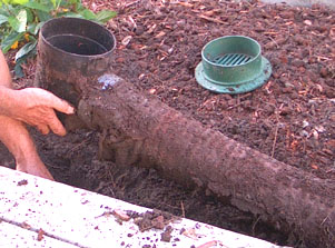 Reinstalling the end point in a French drain next to a driveway.  Photo by Stibolt.